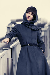 Young fashion woman in gray classic coat and headscarf
