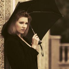 Sad young fashion woman with umbrella on city street