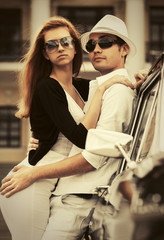 Happy young fashion couple in love leaning on vintage car