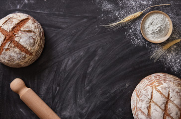 Bakery background. Homemade bread on a black background viewed from above. Top view. Copy space