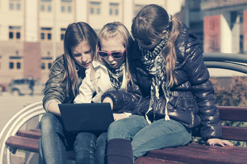 Teen girls using laptop on the bench