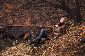 Happy young fashion woman sitting on ground in autumn park