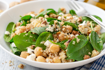 Healthy salad with spinach, chickpeas, quinoa, feta cheese and walnuts in white plate on concrete background. Selective focus.