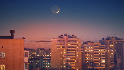 Fotobehang - Beautiful waxing crescent moon setting behind city skyline buildings rooftops at night. Zoom in. Timelapse, 4K UHD.