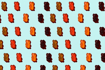 Pattern made of colorful jelly bears on aquamarine background. Flat lay. Minimal concept