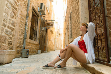 young pretty woman sitting on stairs of old european city