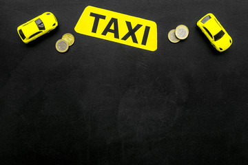 Taxi operator concept. Chip service. Price of services. Sign taxi ner car toy and coins on black background top view space for text