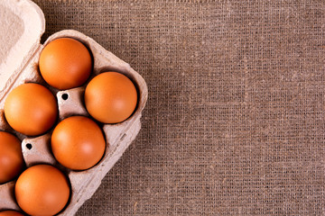 raw chicken eggs in a basket on a jute cloth background