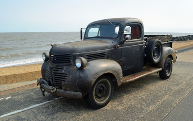 Rusty Classic Piick up truck  parked on seafront promenade.