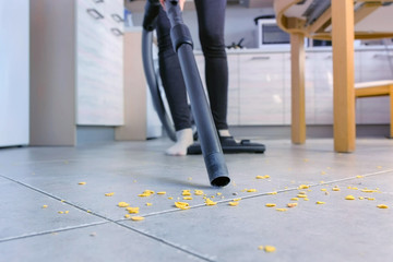 Woman is vacuuming the kitchen floor without brush, only pipe. Legs close-up.