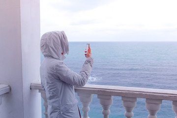Woman in the white jacket shoots sea waves video on smartphone on beautiful terrace with sea view. Back view.