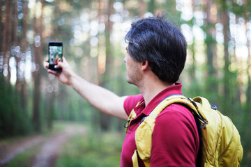 Hiker with backpack taking selfie in the woods