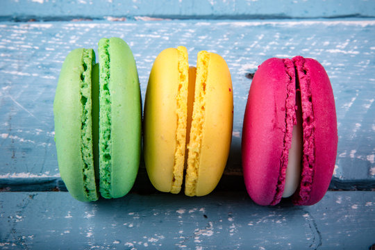 Red, green and yellow macaroons on a weathered blue table