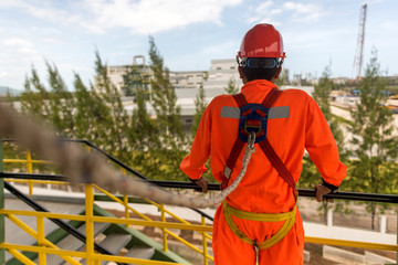 Worker in safety harness on high construction site .
