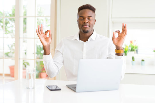 African american business man working using laptop relax and smiling with eyes closed doing meditation gesture with fingers. Yoga concept.