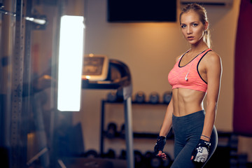 Woman posing while standing in gym. Healthy lifestyle concept.
