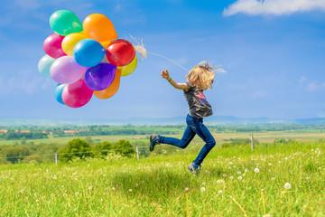 Glückliches Mädchen spring mit vielen bunten Luftballons über eine grüne Wiese