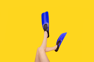 studio photo of female legs in flippers on yellow background, concept of summer sea vacation