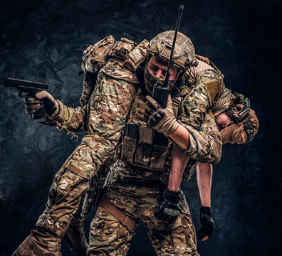 Combat conflict, special mission, retreat. Soldier special forces rescue his wounded teammate carrying him on his shoulders from the battlefield, talking on the radio and calls for support