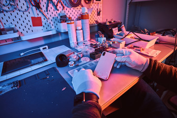 Electronic technician holds a modern smartphone with a broken body sitting at a table in a repair shop. Illumination with red and blue lights
