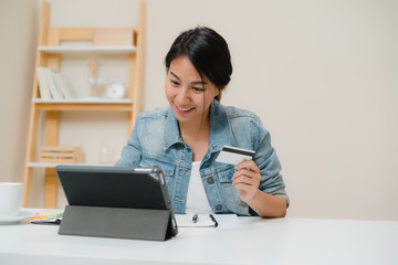 Beautiful smart business Asian woman using tablet buying online shopping by credit card while wear smart casual sitting on desk in living room at home. Lifestyle woman working at home concept.