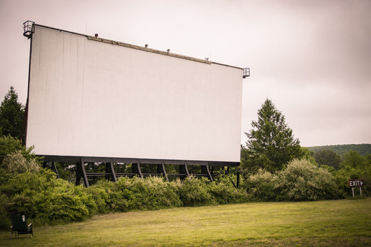 Drive-in theater movie screen stands in the distance; surrounded by grass and wooded overgrowth.