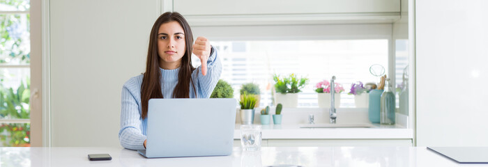 Wide angle picture of beautiful young woman working or studying using laptop with angry face, negative sign showing dislike with thumbs down, rejection concept
