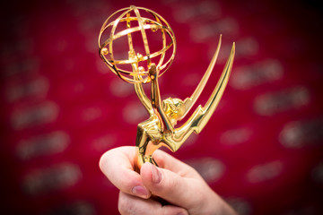 Closeup view of a hand holding an Emmy Award.