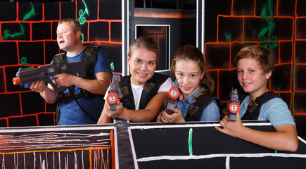 Boy and girls aiming laser guns at other players during laser tag game with parents