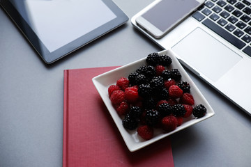 Raspberry and blackberries, healthy lunch in the office. Laptop, tablet, smartphone and notebook on a table