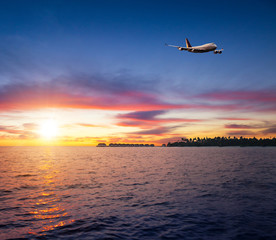 Beautiful sunset on Maldives resort with airplane