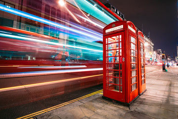 Fototapeten London roten bus Light trails of a double decker bus next to the iconic telephone booth in London