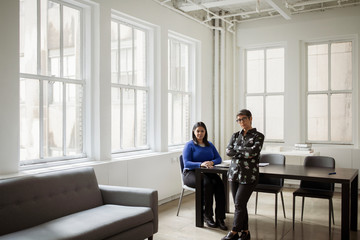Portrait of confident female colleagues by desk against windows in office