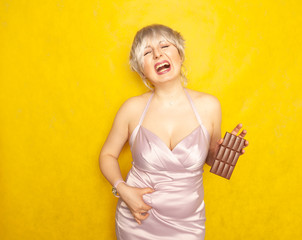 plump woman stands with an unhappy face and a chocolate bar in her hand and touches the fat on her chubby belly on yellow solid studio background