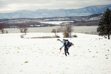 Happy boyfriend carrying girlfriend while running on snow covered field against mountain