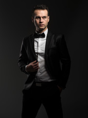 Handsome businessman in suit looking away while standing against black background