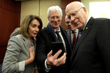 Actor Richard Gere shows some pictures on his phone to House Speaker Nancy Pelosi (D-CA) and Sen. Patrick Leahy