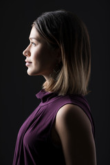 Side view of confident thoughtful woman looking away while standing against black background