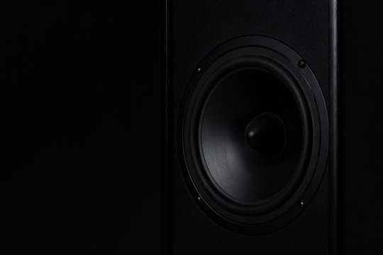 Black Music speaker on a black isolated background. Party or music listening concept.