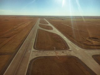 Aerial view of airport runway against sky during sunny day