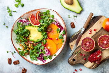 Vegan, detox Buddha bowl with turmeric roasted  chickpeas, greens, avocado, persimmon, blood orange, nuts and pomegranate. Top view, flat lay