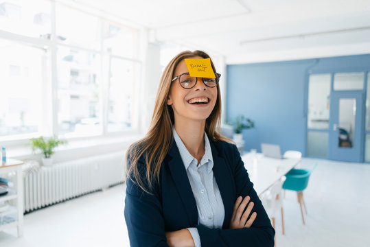 Young businesswoman with yellow sticky note on her forehead, saying 'burnout'