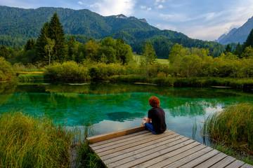 Slovenia, Gorenjska, near Ratece, Sava Dolinka, source, Lake Zelenci, young man sitting on jetty