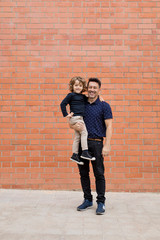 Portrait of smiling father carrying son at brick wall