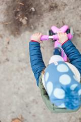 Kind auf pinkem Roller. Kid on little pink scooter.