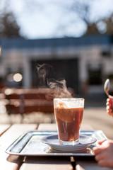 Glass mug with hot chocolate smoking. Glas mit rauchender heißer Schokolade.