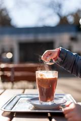 Child hand with cocoa drink in glass outdoor. Kind mit Kakao im Restaurant Garten.