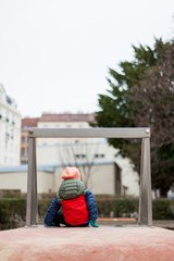 Kind alleine auf Spielplatz in Stadt. Kid alone on playground in city.