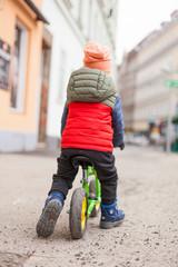 Kind färt mit Laufrad in Stadt. Kid ride balance bike on city street.