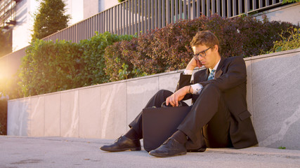 SUN FLARE Young Caucasian man sitting on the street and mourns after being fired
